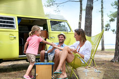 Family camping with a vintage camper van. Happy family relaxing by camper van in summer royalty free stock images