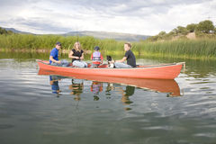 Family in canoe fishing. A family spending time together with thier dog in a canoe on a pond fishing Royalty Free Stock Photos