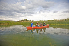 Family in canoe looking. A family with their dog, fishing and spending time together in a canoe on a pond Stock Photography