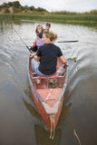 Family in canoe straight on. A family fishing in a canoe Royalty Free Stock Photo