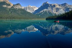 Family canoeing across emerald lake royalty free stock image