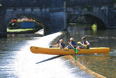 Family canoeing over weir on river Brantome Royalty Free Stock Photos