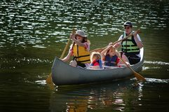 Family Canoeing Together On Lake in Wilderness royalty free stock image
