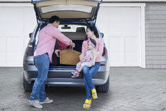 Family on car preparing for holiday. Happy family preparing suitcase and a picnic basket into a car for holiday Stock Image