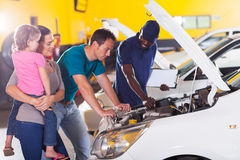 Family car repair. Young family taking their car for repair in garage Royalty Free Stock Image