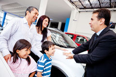 Family with a car salesman Royalty Free Stock Photos