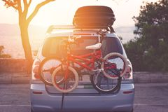 Family car with small kids bicycles rack, ready for travel, making a break on parking. Family car with small red kids bicycles rack, ready for travel, making a stock image