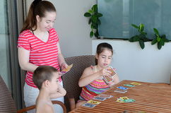 Family card game. Teenage sisters and their younger brother playing a game of cards Royalty Free Stock Image