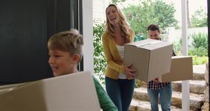 Family with cardboard, boxes entering in a comfortable home 4k