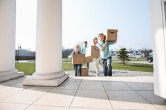 Family with cardboard boxes entering into new house Royalty Free Stock Image
