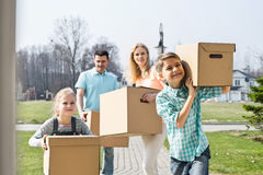 Family with cardboard boxes moving into new house Royalty Free Stock Photography