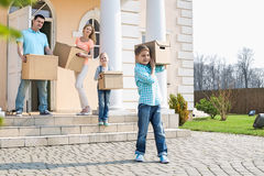 Family with cardboard boxes moving out from house stock photos