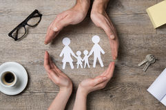 Family care. Close up of female and male hands protecting a paper chain family. Top view of two hands form a circle around white paper chain family on wooden stock photos