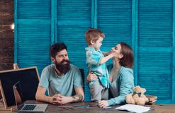 Family cares about education of their son. Parents teaches son, chalkboard on background. Homeschooling concept. Parents. Teaching kid, speaking. Boy listening Stock Photo