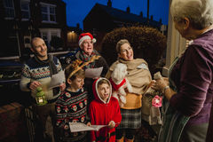 Family Carol Singing. Three generation family are doing door-to-door carol singing. There is a senior women at the door, appreciating their singing Royalty Free Stock Photos