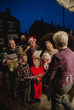 Family Carol Singing. Three generation family are doing door-to-door carol singing. There is a senior women at the door, appreciating their singing Stock Photo