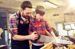 Father and son with saw working at workshop. Family, carpentry, woodwork and people concept - father and little son with saw sawing wood plank at workshop Royalty Free Stock Image