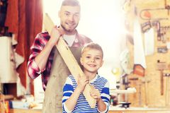 Happy father and son with wood plank at workshop Royalty Free Stock Photography