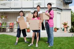 Family carrying boxes into new home Royalty Free Stock Image