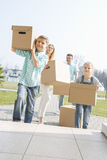 Family carrying cardboard boxes while entering new house Stock Image