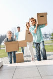 Family carrying cardboard boxes while entering new house Stock Photos