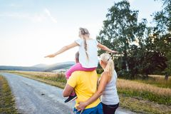 Family carrying child piggyback on summer walk stock photos