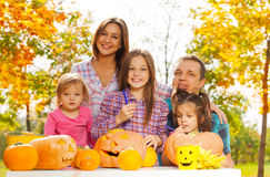 Family carve scary pumpkins in the garden Royalty Free Stock Image