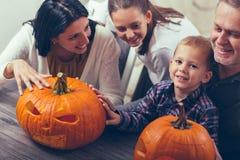 Family carving big orange pumpkin for Halloween Royalty Free Stock Image