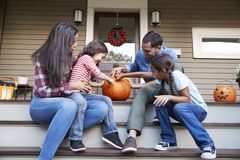 Family Carving Halloween Pumpkin On House Steps royalty free stock photography
