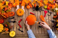 Family carving pumpkin. Halloween trick or treat. Family carving Halloween pumpkin on wooden table with autumn leaves decoration. Top view flat lay of hands and stock image
