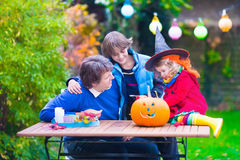Family carving pumpkin at Halloween. Dressed up child trick or treating. Kids and parents trick or treat. Child in witch costume playing in autumn park Royalty Free Stock Image