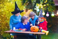 Family carving pumpkin at Halloween. Dressed up child trick or treating. Kids and parents trick or treat. Child in witch costume playing in autumn park Stock Photo