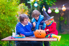 Family carving pumpkin at Halloween. Dressed up child trick or treating. Kids and parents trick or treat. Child in witch costume playing in autumn park Royalty Free Stock Photography