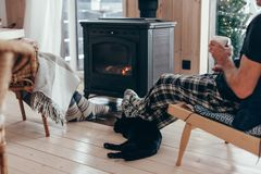 Family with cat relaxing by the fire place. Family and cat relaxing in armchair by the fire place in wooden cabin. Warm and cozy winter holiday concept royalty free stock images