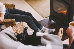 Family with cat relaxing by the fire place. Family and cat relaxing in wicker armchair by the fire place in wooden cabin. Warm and cozy winter holiday concept stock photos