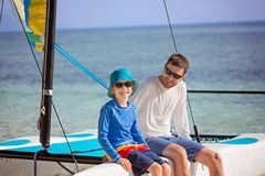 Family at catamaran. Family of two, father and son, enjoying sailing together at hobie cat catamaran, active healthy lifestyle concept Royalty Free Stock Image