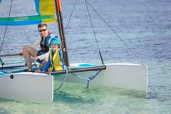 Family at catamaran. Family of two, father and son, enjoying sailing together at hobie cat catamaran, active healthy lifestyle concept Stock Photography