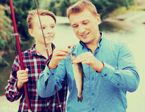 Family with catched fish Stock Images