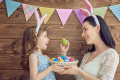 Family celebrate Easter. Mother and her daughter with painting eggs. Happy family celebrate Easter. Cute little child girl wearing bunny ears Stock Images