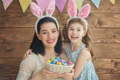 Family celebrate Easter. Mother and her daughter with painting eggs. Happy family celebrate Easter. Cute little child girl wearing bunny ears Stock Photography