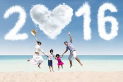 Family celebrate new year on the coast. Joyful asian family celebrating new year on the beach, jumping together under cloud shaped numbers 2016 Royalty Free Stock Photography