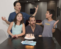 Family celebrating a birthday. A middle-aged caucasian bearded male is sitting behind his birthday ice cream pie with candles lit.  His Korean wife and Amerasian Royalty Free Stock Photography