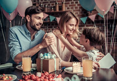 Family celebrating birthday. Family celebrating mother`s birthday in decorated kitchen. Little boy is hugging his mom, all are smiling Stock Photography