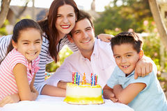 Family Celebrating Birthday Outdoors With Cake stock images