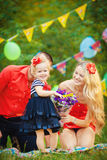 Family celebrating birthday party in green park outdoors Stock Photos