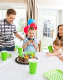 Family Celebrating Boy's Birthday At Home. Boy holding delicious cupcake with family celebrating his birthday at home Stock Image