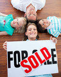 Family celebrating buying their new house. Happy family celebrating buying their new house lying on the floor Stock Image