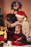 Family celebrating Christmas at home. Happy family decorating Christmas tree with balls sitting on the floor in the house. Concept of New Year miracle and dream royalty free stock images