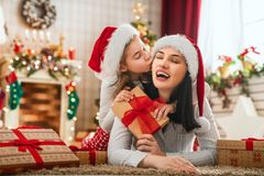 Family celebrating Christmas. Merry Christmas and Happy Holidays! Cheerful mom and her cute daughters girls exchanging gifts. Parent and little children having royalty free stock images