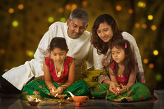 Family celebrating Diwali. Indian family in traditional sari lighting oil lamp and celebrating Diwali, fesitval of lights inside a temple. Little girl hands